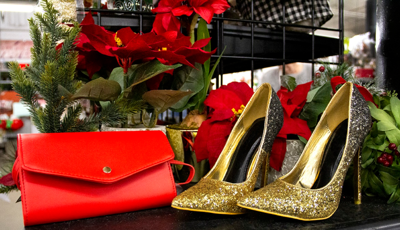 Glittery gold high heels and a red purse with poinsettias.